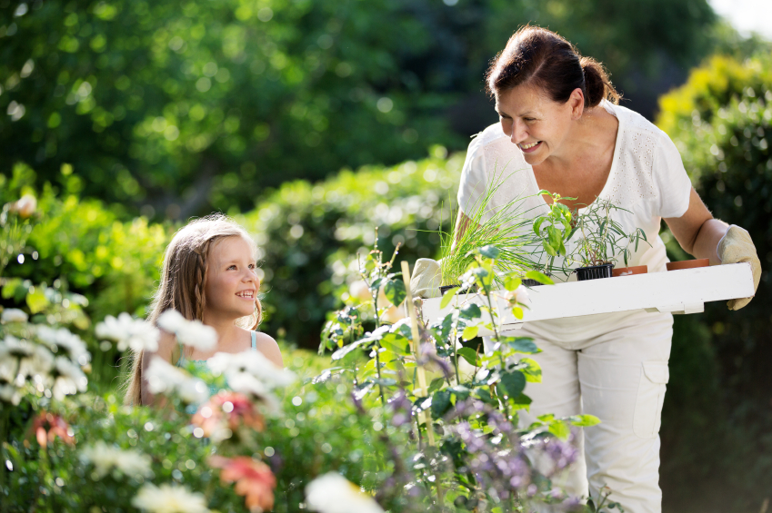 Girl and mother planting herbs in garden