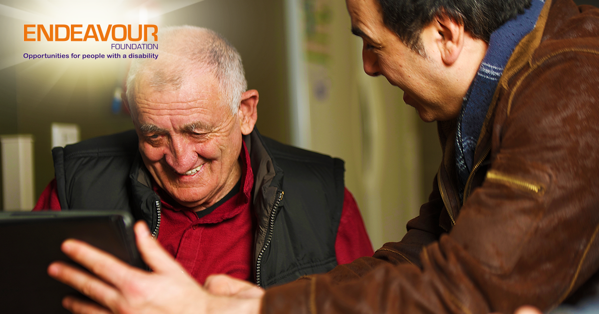 An elderly man laughing with a young man