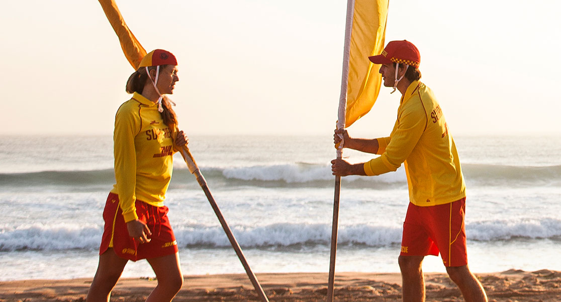 Surf Life Savers holding red and yellow flags.