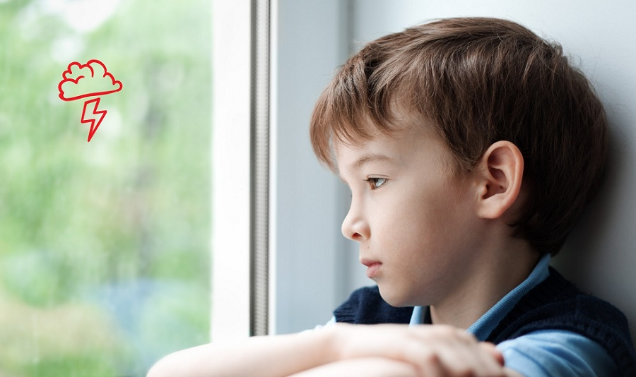 Sad boy looking out of a window.