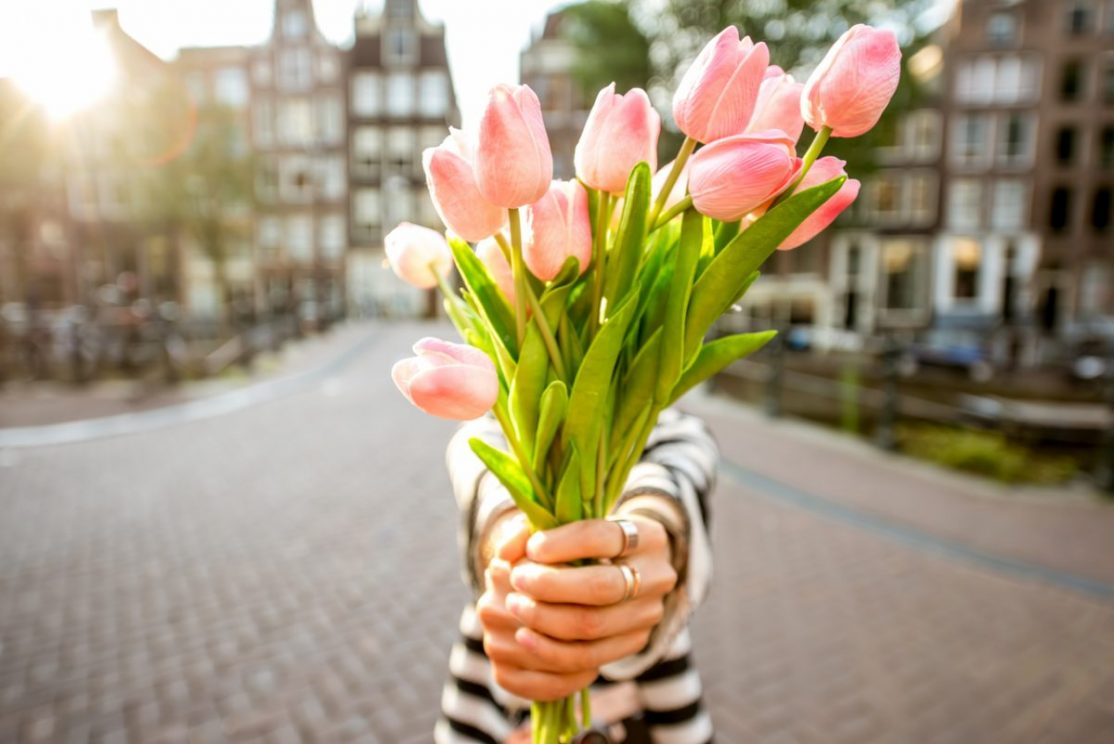 Woman giving a beautiful bouquet of pink tulips standing outdoors