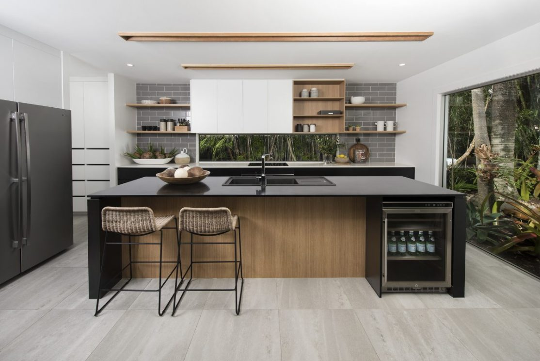 Modern kitchen with appliances, pantry and wine fridge.